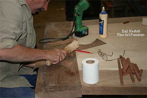 Earl pounding pegs into tenons at end of custom made dining table